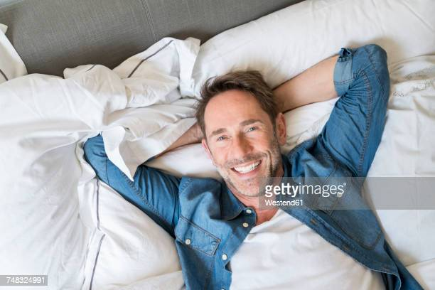 Portrait of happy mature man lying on bed with hands behind head
