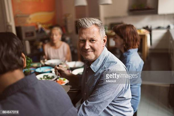 Portrait of happy mature man sitting with friends at table