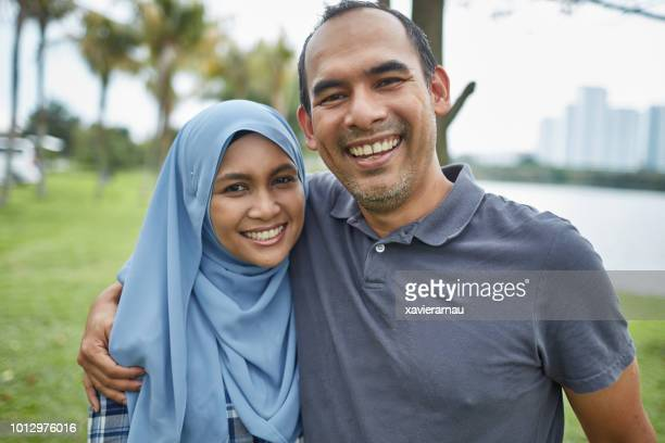 Portrait of happy mature Muslim couple at park