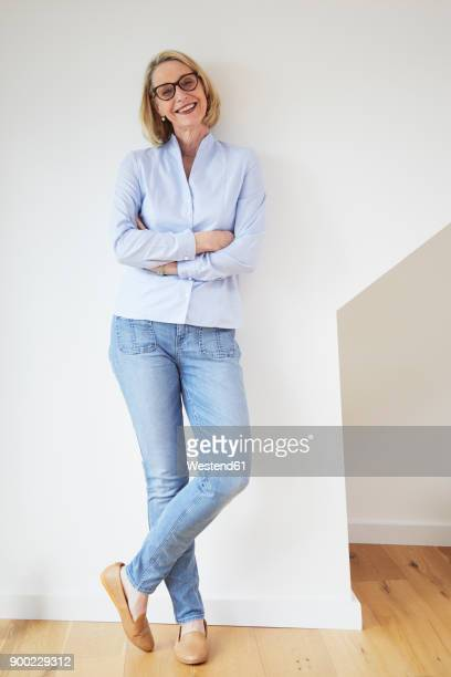 portrait of happy mature woman at home - ganzkörperansicht stock-fotos und bilder
