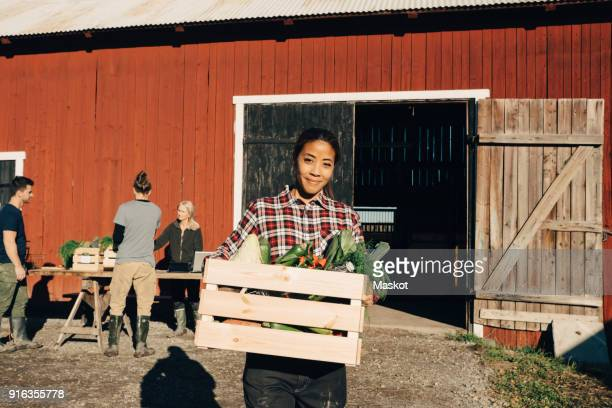 Portrait of happy mature woman carrying crate full of vegetables with barn in background