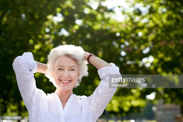 portrait of happy mature woman in nature - hand in hair stock pictures, royalty-free photos & images