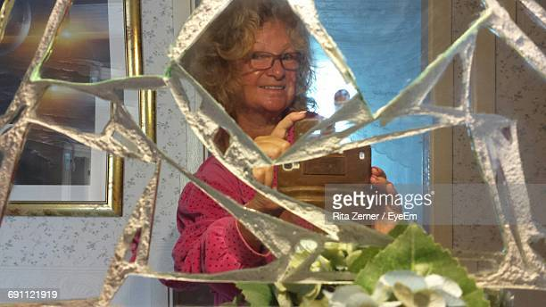 Portrait Of Happy Mature Woman Photographing While Reflecting On Broken Mirror