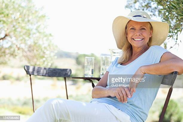 portrait of happy mature woman sitting in chair - sun hat stock pictures, royalty-free photos & images