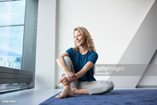 Portrait of happy mature woman sitting on carpet at home looking through window