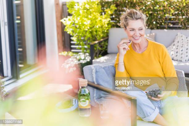 portrait of happy mature woman sitting on terrace eating blueberries - beautiful people stock pictures, royalty-free photos & images