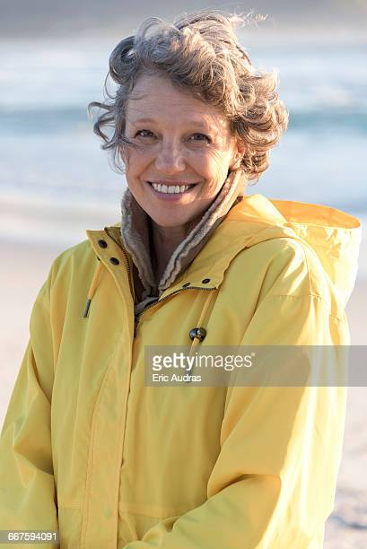 portrait of happy mature woman smiling on the beach - coat stock pictures, royalty-free photos & images