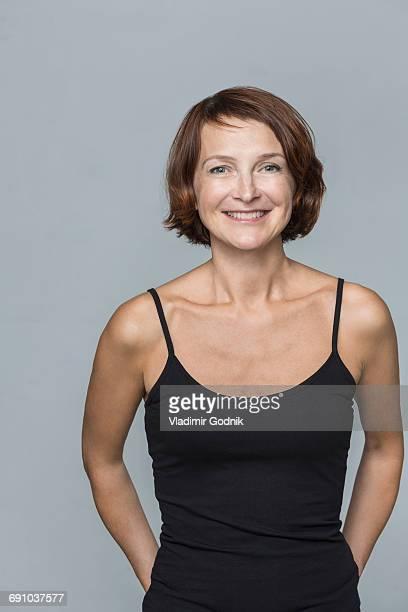 portrait of happy mature woman standing against gray background - hände hinter dem kopf stock-fotos und bilder