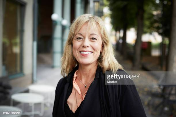 portrait of happy mature woman standing by sidewalk cafe - medium length hair stock pictures, royalty-free photos & images