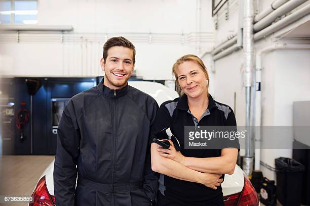 Portrait of happy mechanic standing with female in auto repair shop