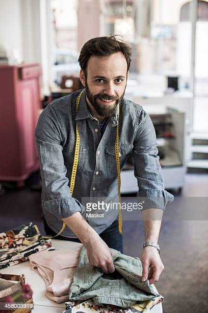 Portrait of happy mid adult male design professional working at table in studio