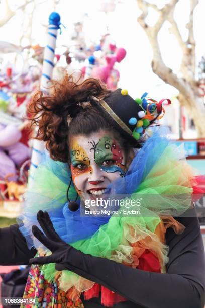 portrait of happy mid adult woman in face paint standing outdoors - clown stock-fotos und bilder