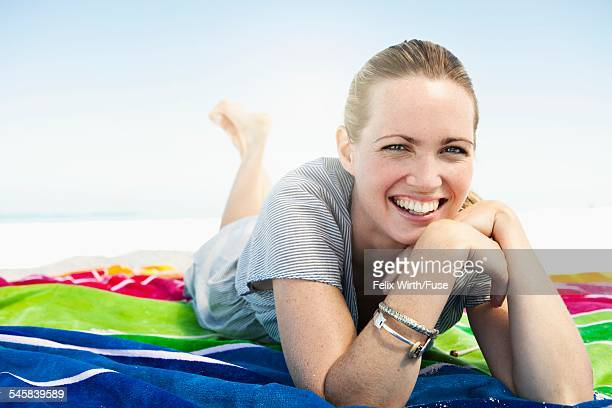 Portrait of happy mid adult woman lying on beach towel