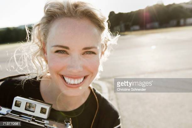 Portrait of happy mid adult woman with vintage camera
