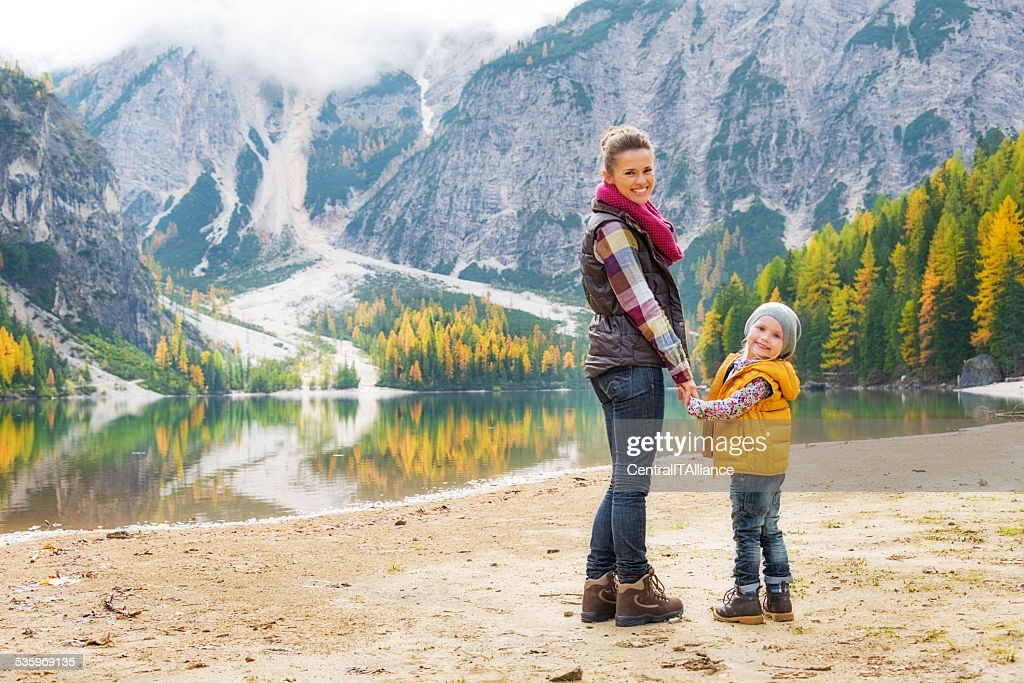 Portrait of happy mother and baby on lake braies, italy : Stock Photo