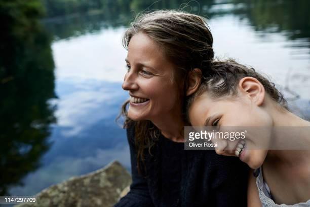portrait of happy mother and daughter at a lake - frauen über 30 stock-fotos und bilder