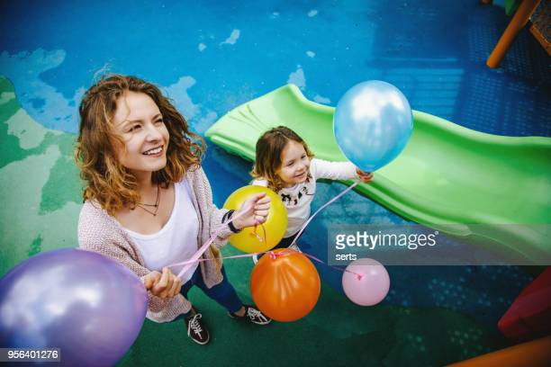 portrait of happy mother and daughter having fun playground - preschool building stock pictures, royalty-free photos & images