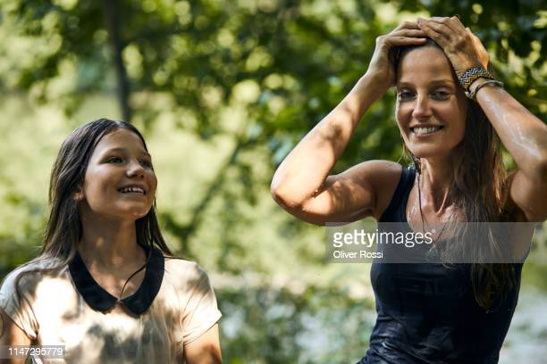 portrait of happy mother and daughter with wet hair outdoors in summer - women in wet t shirts stock pictures, royalty-free photos & images