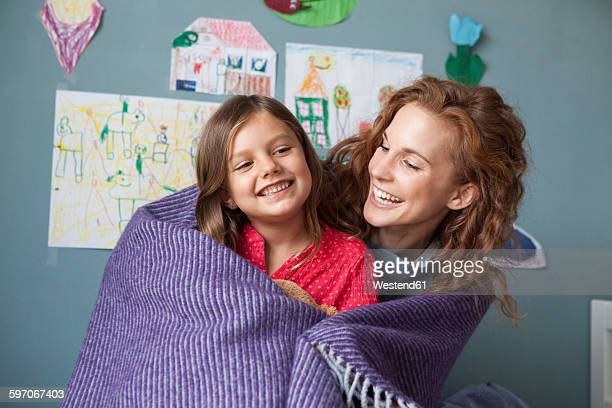 Portrait of happy mother and little daughter together in childrens room