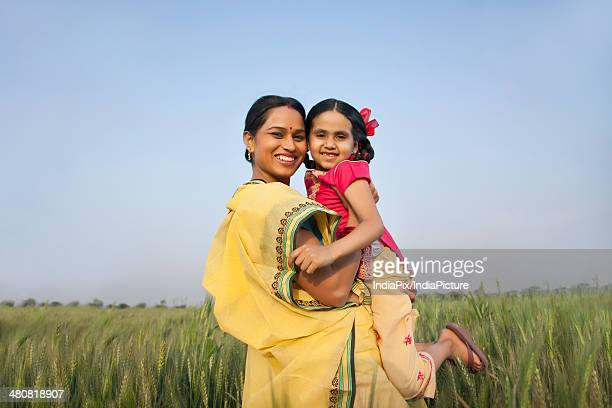 Portrait of happy mother lifting daughter in wheat field against blue sky