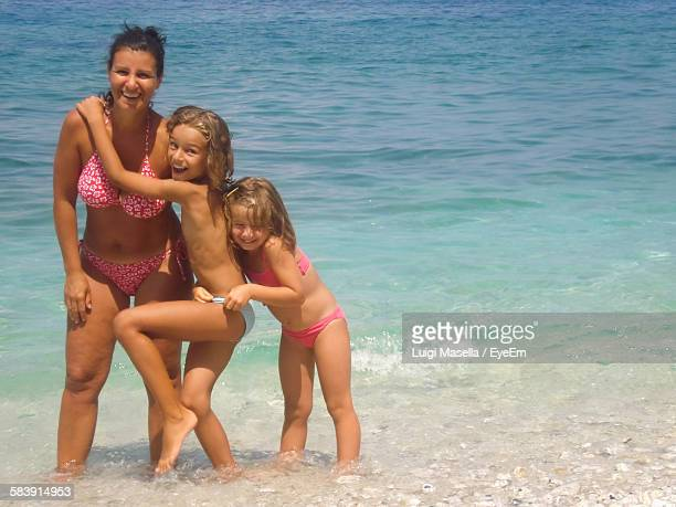 portrait of happy mother with daughters at beach - 8 9 anos - fotografias e filmes do acervo
