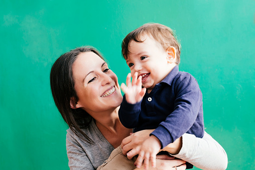 Portrait of happy mother with her little son in front of green background - gettyimageskorea