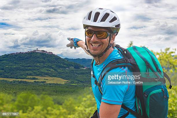 Portrait Of Happy Mountain Biker Pointing At Mountain