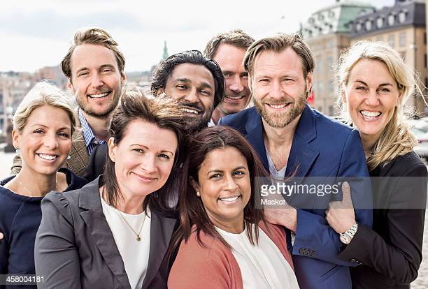Portrait of happy multi-ethnic business people standing together outdoors
