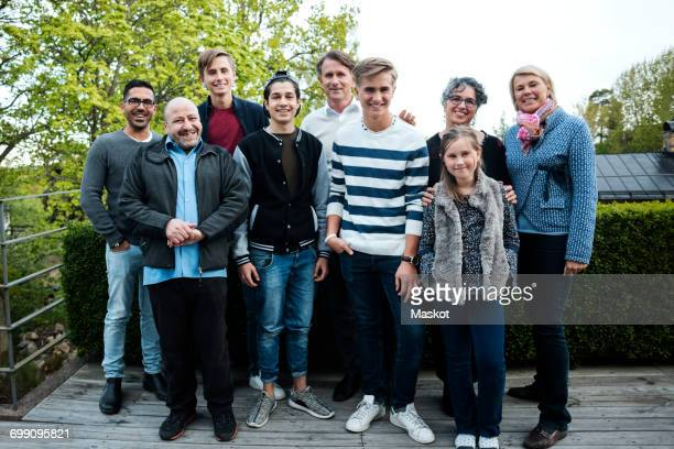 portrait of happy multi-ethnic friends and family standing against hedge in yard - large family stock pictures, royalty-free photos & images