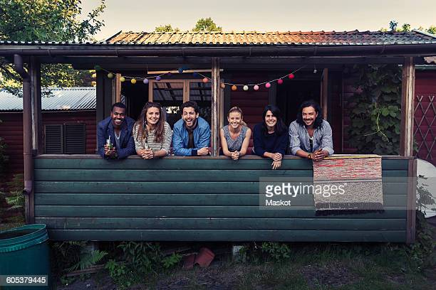 Portrait of happy multi-ethnic friends standing on porch at log cabin