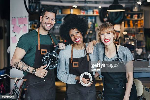 Portrait of happy multi-ethnic mechanics with gears in workshop