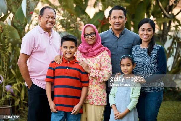 portrait of happy multi-generation family in yard - malaysian ethnicity stock pictures, royalty-free photos & images