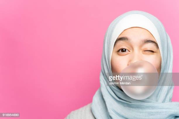 portrait of happy muslim girl with chewing gum - islam fotografías e imágenes de stock