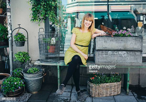Portrait of happy owner leaning on crate outside plant shop
