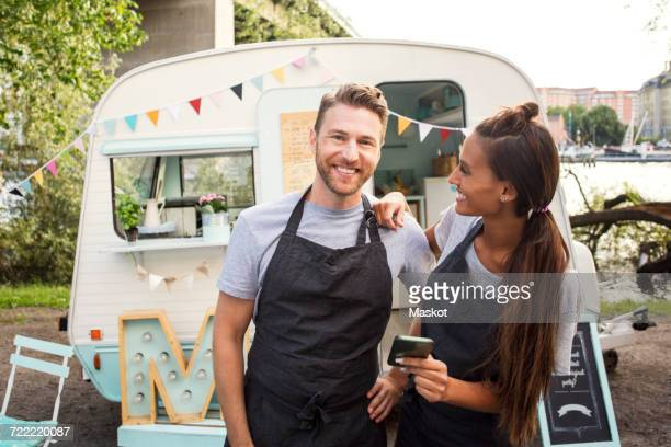 portrait of happy owner standing with female colleague outside food truck on street - happy merchant stock pictures, royalty-free photos & images