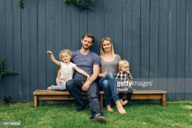 Portrait of happy parents and children sitting on seats against fence at yard