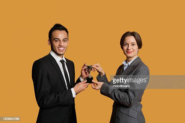 portrait of happy partners holding winning trophy together - holding trophy stock pictures, royalty-free photos & images