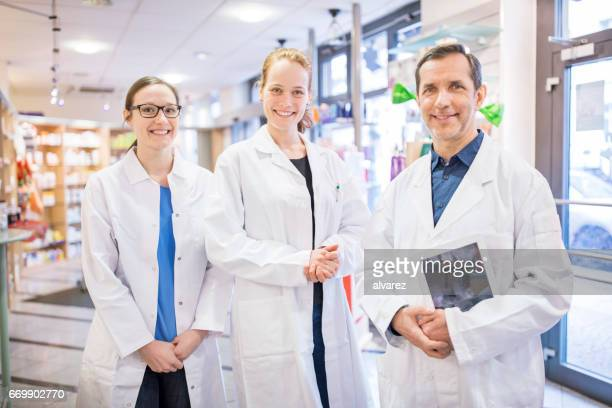 Portrait of happy pharmacists standing in store
