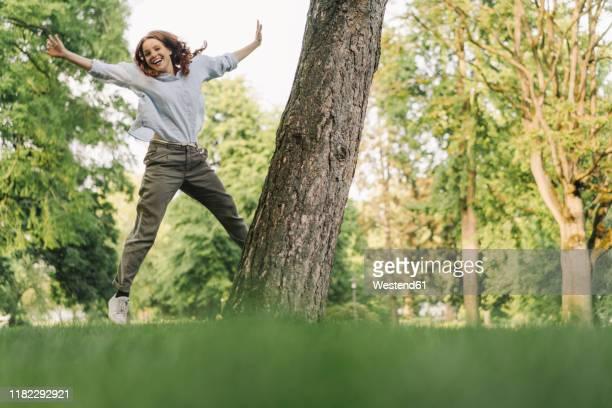 portrait of happy redheaded woman in a park - erwachsener über 30 stock-fotos und bilder