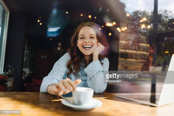 portrait of happy redheaded woman with laptop in a cafe - café stock-fotos und bilder