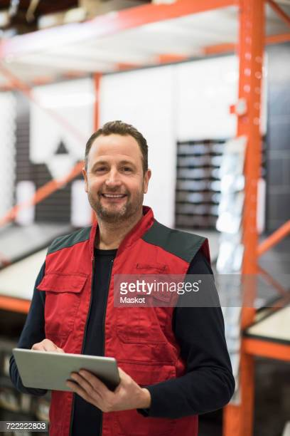Portrait of happy salesman holding digital tablet while standing in hardware store