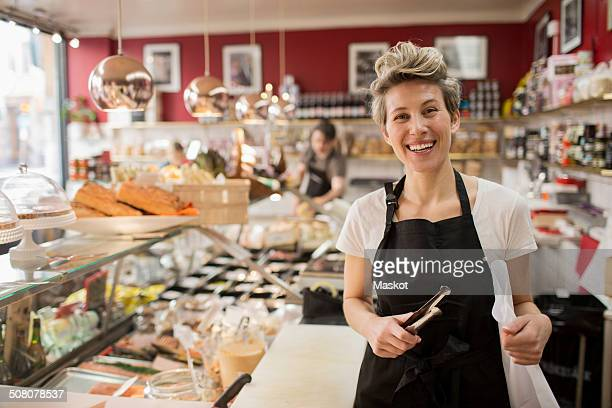 portrait of happy saleswoman cutting cheese at counter in supermarket - delicatessen stock pictures, royalty-free photos & images