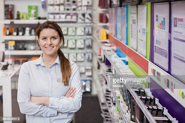 portrait of happy saleswoman standing in store - saleswoman stock photos and pictures