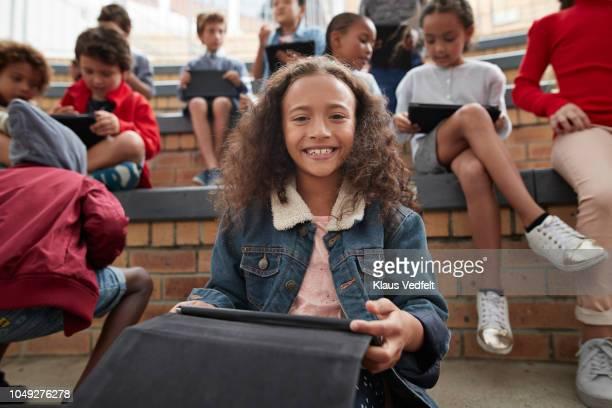 portrait of happy schoolgirl having class outside with digital tablet - écolière photos et images de collection