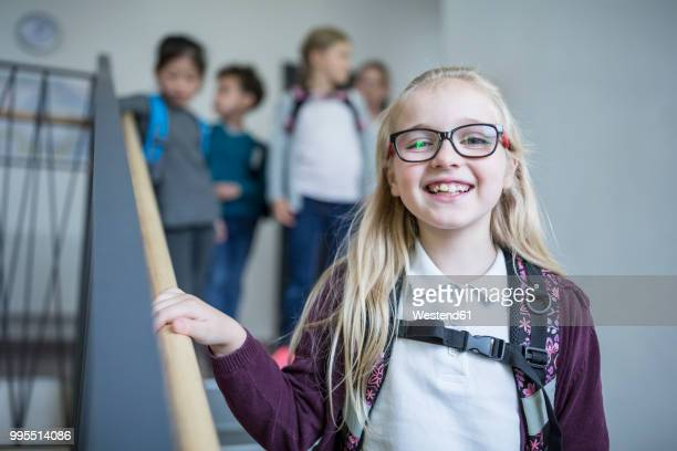 Portrait of happy schoolgirl with classmates on staircase leaving school