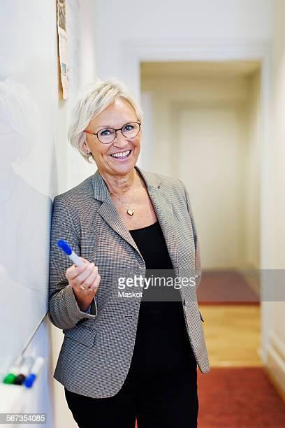 Portrait of happy senior businesswoman giving presentation in office
