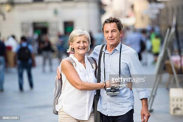 Portrait of happy senior couple on city trip