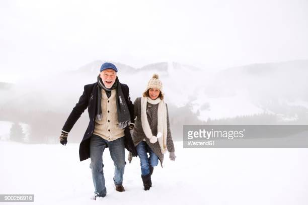 Portrait of happy senior couple walking in snow-covered landscape