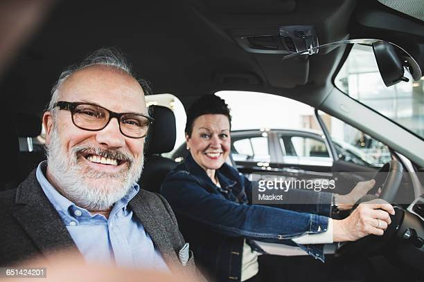 Portrait of happy senior man and woman sitting in car at showroom