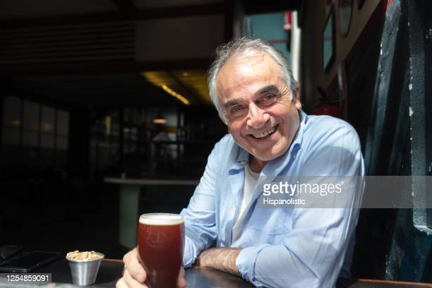 portrait of happy senior man at a pub enjoying a beer on a sunny day while smiling at camera - one man only stock pictures, royalty-free photos & images